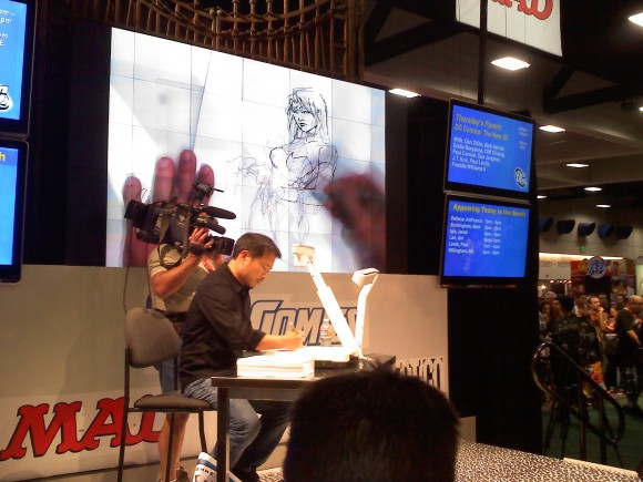 Co-publisher of DC Comics, Jim Lee, sketches on stage while fans look on.