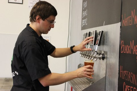 8-Bit Brewery co-owner Ryan Whitten fills a glass from their NES controller bar taps.