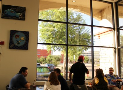 Patrons relax by the large windows at 8-Bit with their favorite beers.
