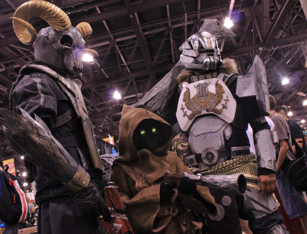 A Destiny Warlock and Titan pose with a Star Wars jawa on the exhibitor floor.