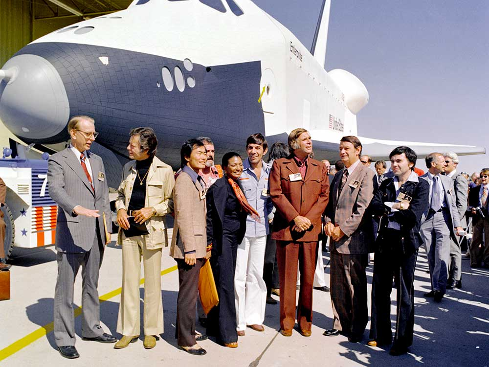 The Shuttle Enterprise rolls out of the Palmdale manufacturing facilities with Star Trek television cast members and creator Gene Roddenberry.