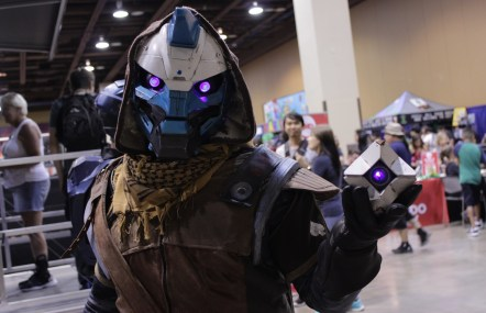 A Cayde-6 cosplayer holding his ghost.