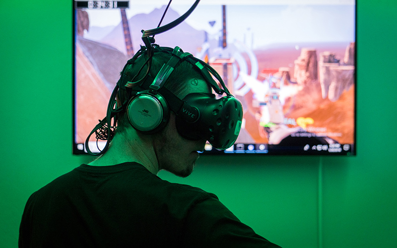 "Tyler Powell, a first-time VR player, paid a dollar per minute he to use the arcade's HTC Vive headset and be fully immersed in the game ""Skyfront"" with his friends. (Photo by Daria Kadovik/Cronkite News)"
