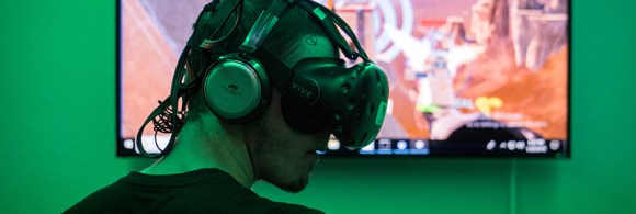 """Tyler Powell, a first-time VR player, paid a dollar per minute he to use the arcade's HTC Vive headset and be fully immersed in the game """"Skyfront"""" with his friends. (Photo by Daria Kadovik/Cronkite News)"""