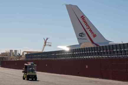 A golf cart drives by a Honeywell Boeing 757 parked at Phoenix Sky Harbor International Airport. (Photo by Nick Serpa/Cronkite News)