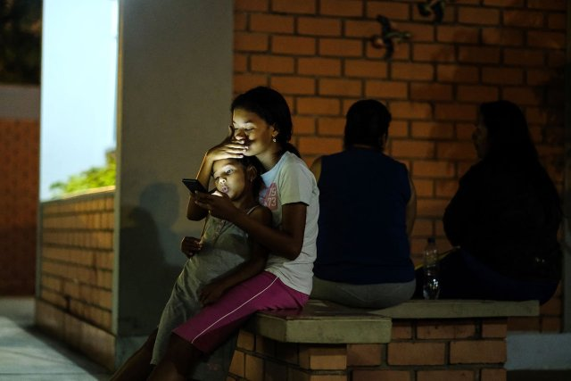 Andreina Iyala, 15, and another young girl check a cellphone while staying in a shelter in Lima, Peru. Smartphones can be a lifeline for migrants. (Photo by Chloe Jones/Cronkite Borderlands Project)