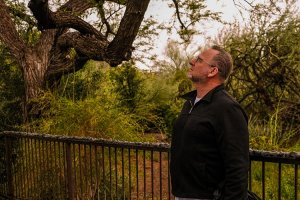 """Garth Paine listens at the Desert Botanical Garden, where the natural world abuts the urban environment. """"We have insects and birds chirping being absorbed by the plants, but we also have planes and cars from the freeway behind us reverberating off the buildings and cement."""" (Photo by Chloe Jones/Cronkite News)"""