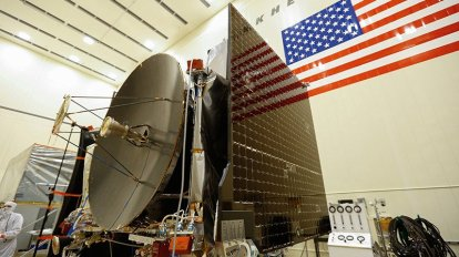 """Final assembly in 2015 of the OSIRIS-REx spacecraft, which launched in 2016. University of Arizona teams had been working on the project for more than a decade when it reached a near-Earth asteroid, Bennu, this week and executed a touch-and-go mission to briefly """"tag"""" the surface, collect soil samples and head back to orbit. (Photo courtesy Lockheed Martin)"""