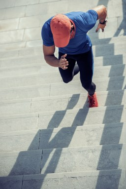 Close up of young man running up the stairs.