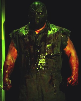 Lucha Underground's Matanza stands in a darken open doorway covered in the blood of his victims