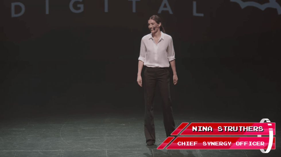 "A smiling woman with a headset stands on a stage in a white shirt and dress slacks, about to perform a presentation. A title card says her name is Nina Struthers and that she is ""Chief Synergy Officer"""