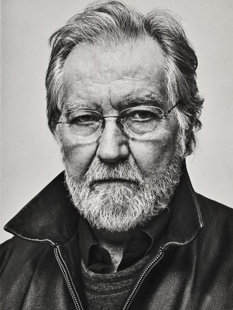 a black and white photograph of an older Tobe Hooper, director of The Texas Chainsaw Massacre and Poltergeist. He is seen from the neck up wearing a jacket with the collar turned up, he has glasses and a white full face beard