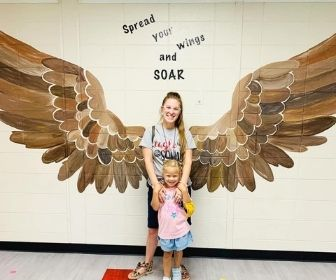 Two pose for photo with eagle wings