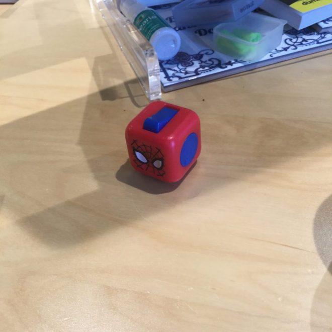 Een fidget cube met Spiderman-opdruk