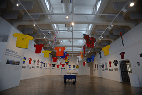 An installation shot of a current exhibition at the Riverside, CA Art Museum of my collection of vintage shirts of the 32 teams in the World Cup along with photographs of stadiums and club shirts from Argentina, England, Portugal, Scotland, the United States and Uruguay.