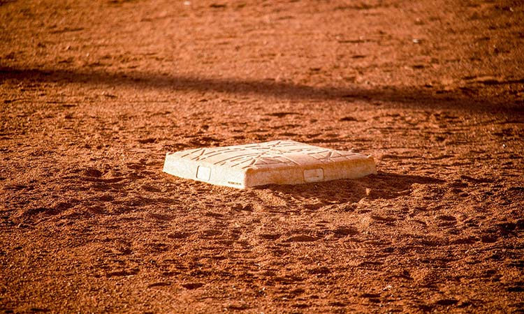 A baseball base on sandy ground on a baseball field