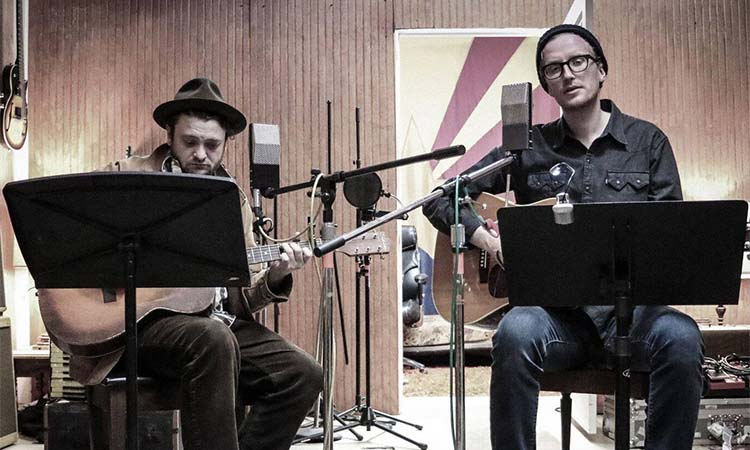 The Lost Brothers are playing two guitars and sitting in front of microphones and sheet music in a recording studio