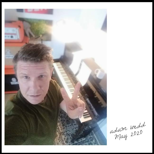 Adam Wedd gives the V peace sign to the camera, he's standing in front of a piano