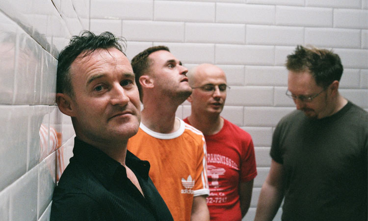 Promo shot of Irish band Blink, the band are standing in front of a wall with while tiles