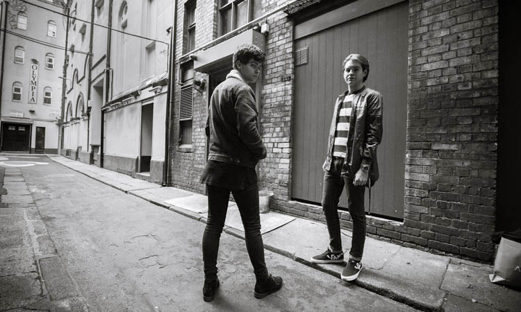 The band Hawke in a black and white image, standing in a side street