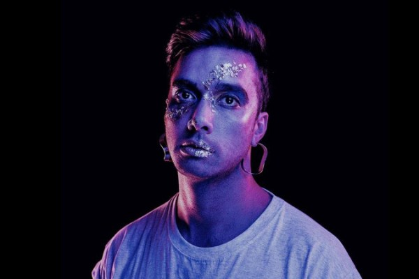 Dyvr promo shot, with glitter make up standing in purple light on black background