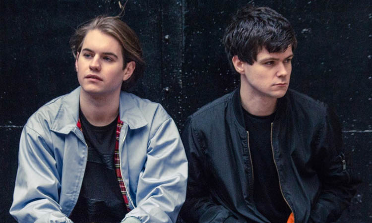 Band photo of 'Hawke', two young guys looking in opposite directions, they are in front of a dark wall