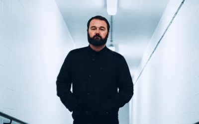Maddox Jones Promo shot, man with a beard wearing dark clothes in a white corridor