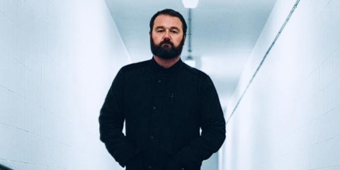 Maddox Jones Promo shot, man with a beard wearing dark clothes in a white corridor