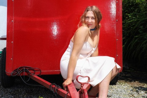 Aine Duffy is wearing a white dress sitting pn the crowbar of a horsebox painted red
