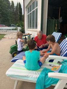 Un abuelo jugando a las cartas con sus nietos.