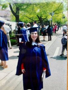 A young woman dressed in university regalia