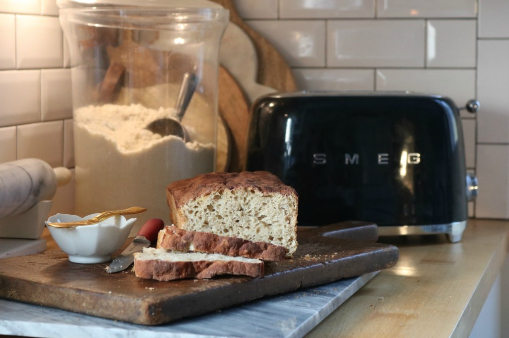Artisan apple bread on a cutting board, sitting on a kitchen counter next to a toaster, and a glass canister full of flour.