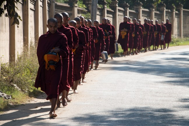 Monks walking with their food powls