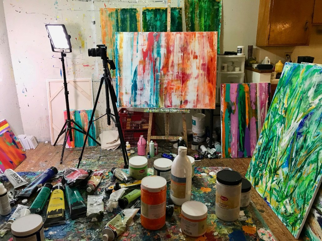 Nestor Toro's studio with works in progress and materials such as tubes of acrylic paint