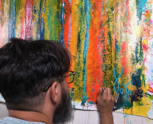 "Artist Nestor signing his work ""Fearlessness"""