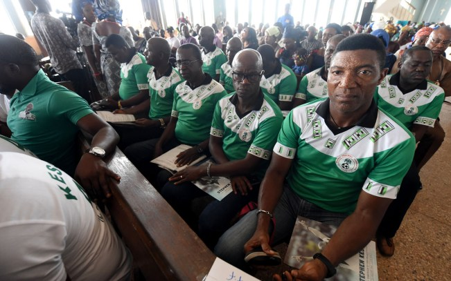 Nigerian former captain and goalkeeper Peter Rufai (R) sits with former international football players during the funeral ceremony of late Nigerian football legend Stephen Keshi at the Evangelist Catholic Church of St John, in Illah, Delta State, on July 29, 2016. Former Nigerian international and coach Stephen Keshi died from a heart attack at the age of 54 on June 2016. Keshi, also a former skipper of Nigeria, won the Africa Cup of Nations as a player in 1994 and coach in 2013. / AFP PHOTO / PIUS UTOMI EKPEI