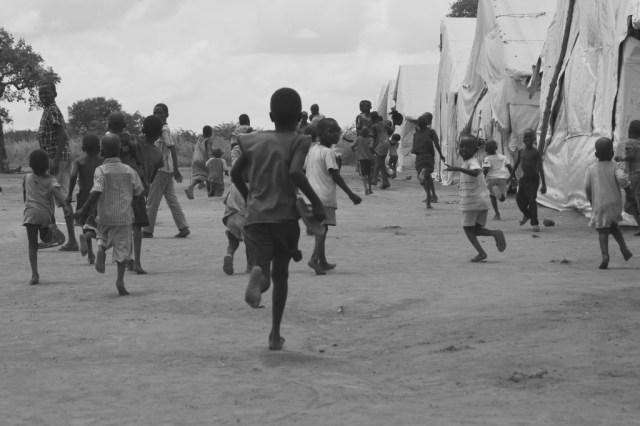 """Flygtningelejren Adjumani i det nordlige Uganda, var engang verdens største. I dag bor her """"kun"""" 70.000 mennesker, hvoraf 80 procent er uledsagede børn. Deres forældre er ofte blevet slået ihjel eller kidnappet af rivaliserende stammer i den sudanesiske borgerkrig. Det er ikke unormalt at halvstore piger ankommer alene over grænsen med små børn på hoften. I en særlig modtagelejer rehabiliteres flygtningene i tre måneder, før de integreres i den almindelige lejr.  PRfoto."""