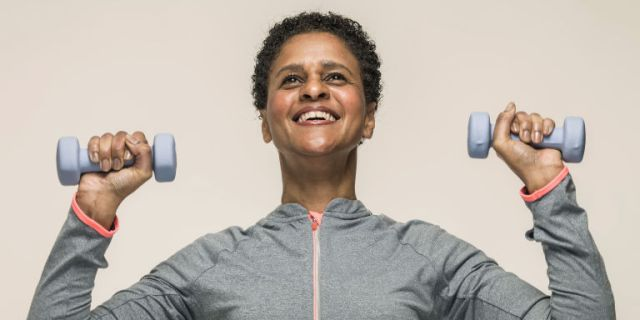 Mature black woman lifting weights at the gym