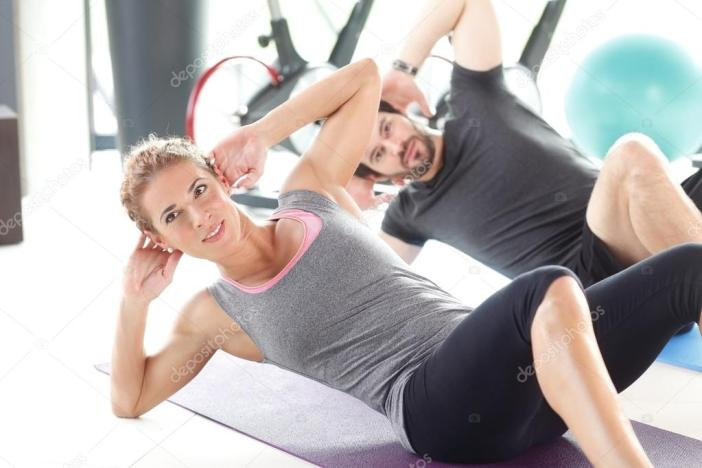 Man and woman training together at the gym