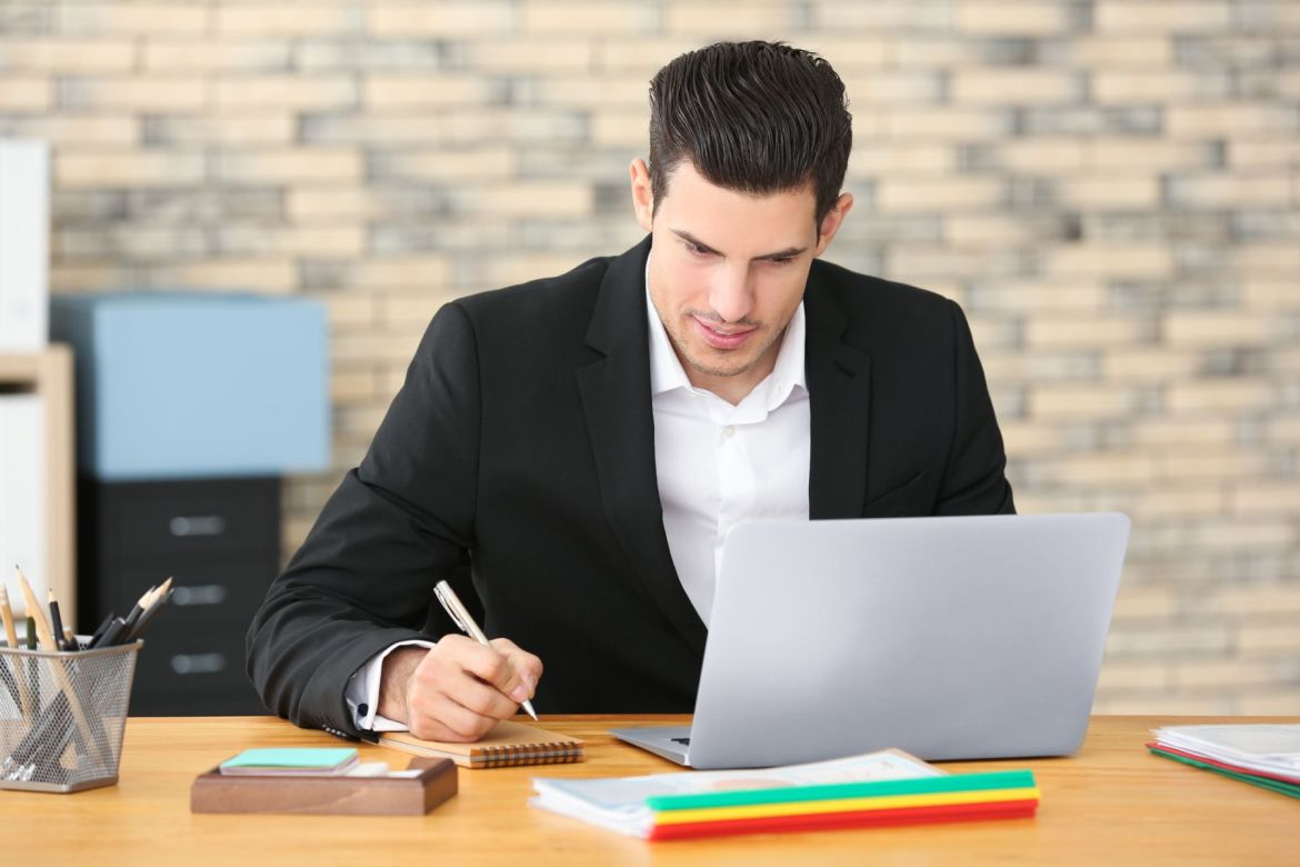 man at a desk with his laptop getting things done