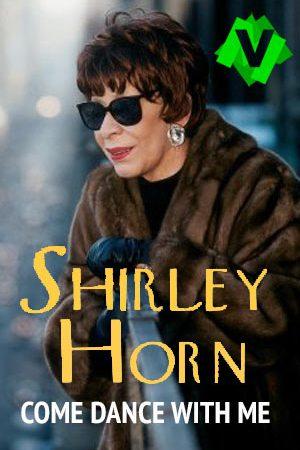 Shirley Horn con abrigo de pieles y con gafas de sol apoyada en la barandilla de un balcon mira la calle
