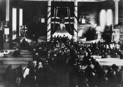 Eid kyrkje blei brukt som vallokale i Eid kommune  i Sogn og Fjordane ved folkerøystingane i 1905. Dette biletet er frå folkerøystinga på spørsmålet om unionsoppløysinga. Kyrkja var pynta med flagg, blomekransar og bjørkelauv. (Kjelde: www.sffarkiv.no)