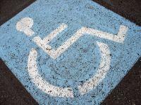 Et slidt handicapsymbol med hvid kørestol på blå baggrund, malet på jorden