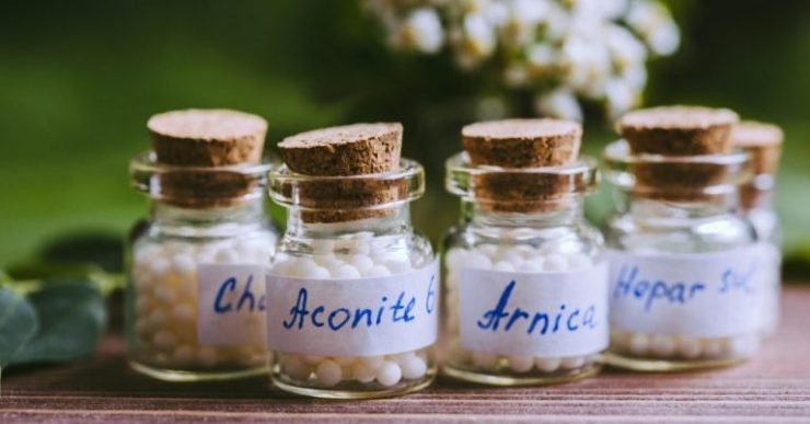 The image shows four common homeopathic remedies in glass bottles.