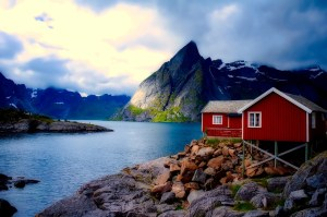 Norwegischer Fjord mit dramatischer Beleuchtung, einem Kegelberg und ochsenblutfarbenem Haus