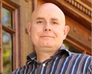 Ein freundlich aussehnder, kahlköpfiger Mann im Portrait