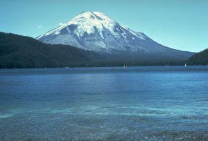 ein spitzer, oben schneebedeckter Bergkegel vor einem blauen See