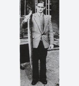Ein Mann in einem feinen Anzug hält einen großen, toten Aal hoch