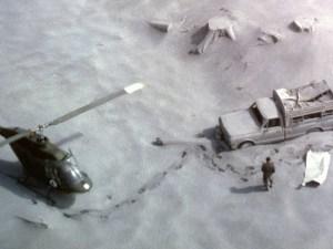 Luftbild eines Hubschraubers, der neben einem Kleinlaster gelandet ist. Es gibt tiefe Spuren im Staub und einen abgedeckten Leichnam