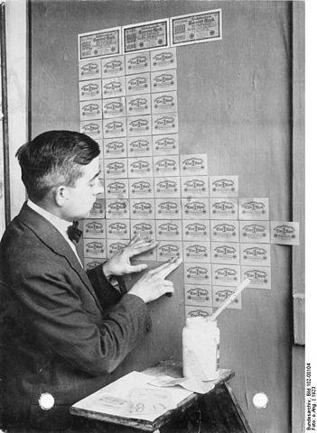Tapezieren einer Wand mit Einmarkscheinen, die zum Zeitpunkt der Hyperinflation 1923 in Deutschland deutlich billiger waren als eine Tapete. (Foto: Bundesarchiv; Bild 102-00104; )